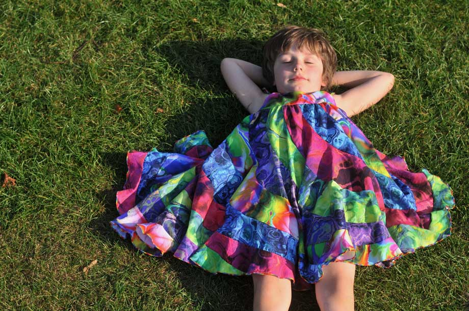 Child laying in the glass in a peppermint swirl dress made of rainbow paint pour fabrics